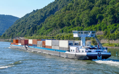 stacking cargo containers on large barge on the Rhine River