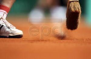 Court staff brush clay off the tramlines on Court Philippe Chatrier during third round action for the French Open tennis tournament at Roland Garros in Paris, France, 27 May 2011. EPA/KERIM OKTEN