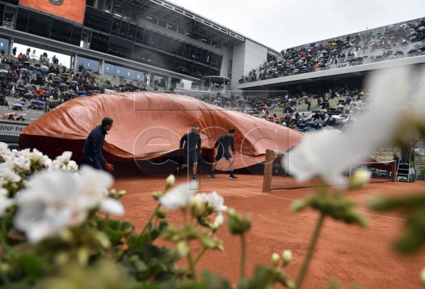 Staff covers the Court Philippe Chatrier as rain interrupts Dominic Thiem of Austria playing Novak Djokovic of Serbia during their men?s semi final match during the French Open tennis tournament at Roland Garros in Paris, France, 07 June 2019.  EPA-EFE/JULIEN DE ROSA