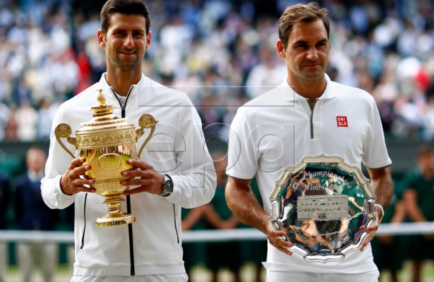 Novak Djokovic of Serbia (L) with the championship trophy after defeating Roger Federer of Switzerland (R) in the men's final of the Wimbledon Championships at the All England Lawn Tennis Club, in London, Britain, 14 July 2019. EPA-EFE/NIC BOTHMA EDITORIAL USE ONLY/NO COMMERCIAL SALES