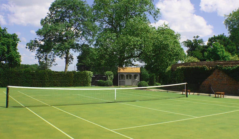 Mature trees fringe a tennis court built by En Tout Cas