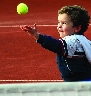 Young boy playing on Omniclay synthetic clay tennis court surface by en Tout Cas