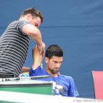 Djokovic with trainer working on shoulder