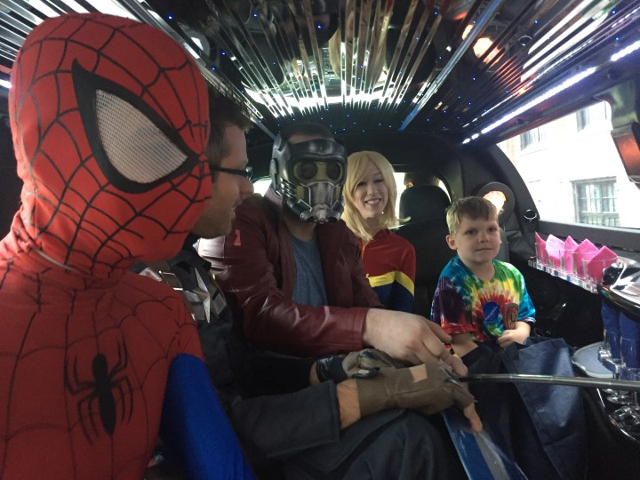 Superheroes with a Wish Kid in a limo