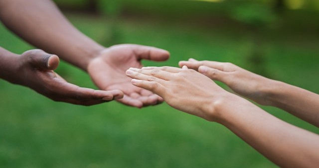Diverse male and female hands stretch to each other, green grass background
