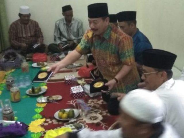Herman HN membantu membagikan Al Quran usai acara haul 40 hari wafatnya K.H. Muhammad Sobari di Ponpes Al Hikmah Bandarlampung, Minggu, 17 Juni 2018.