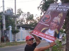 Pengurus PAC PDIP Juwana membersihkan poster Jokowi Raja. (Foto : Alwi Alaydrus/krjogja.com)