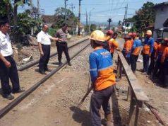 Para pekerja sedang menutup perlintan sebidang (jalan pintas) di perlintasan kereta di wilayah Kelurahan Jababaya 2 - Kelurahan Surabaya, Bandarlampung.