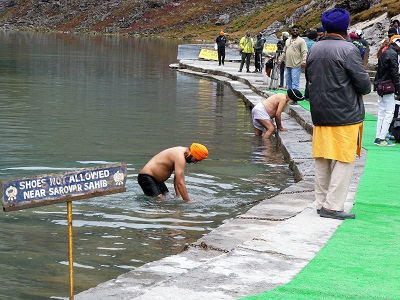 Sikh men paying homage in the lake water at Hemkund