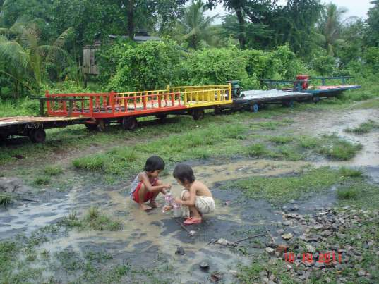 Children playing in the puddles beside Bamboo Train (Norry)