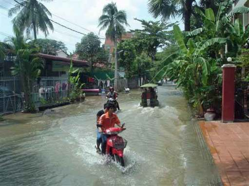 Motor-bikes-plow-through flow of water in main streets after rain
