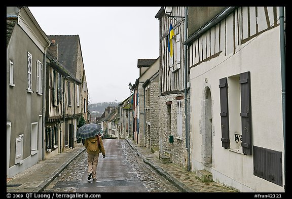 Picture/Photo: Pedestrian with umbrella in narrow street ...