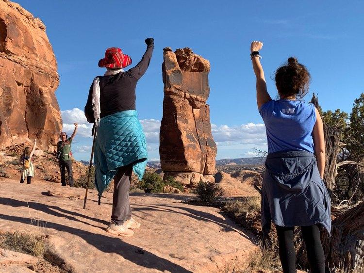 Women in the desert raising fists