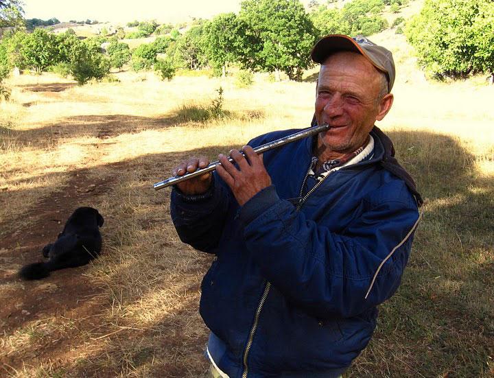 Older man playing flute. Photo by Julian Hoffman.