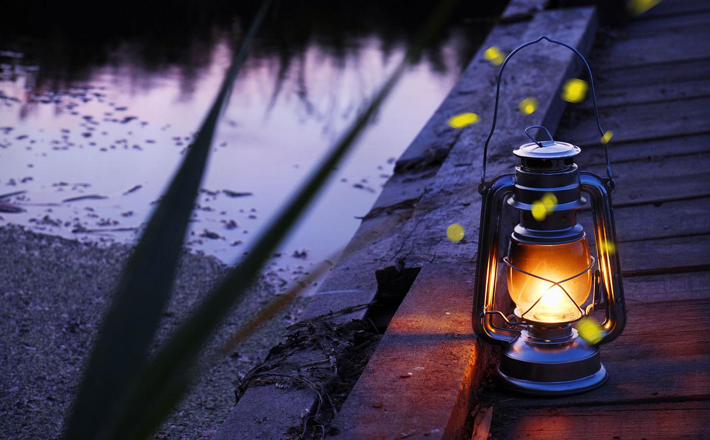 Hurricane lamp at twilight next to river