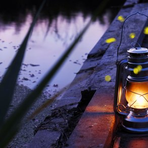 Hurricane lamp at twilight next to river