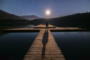 Man on dock with long shadow caused by moon