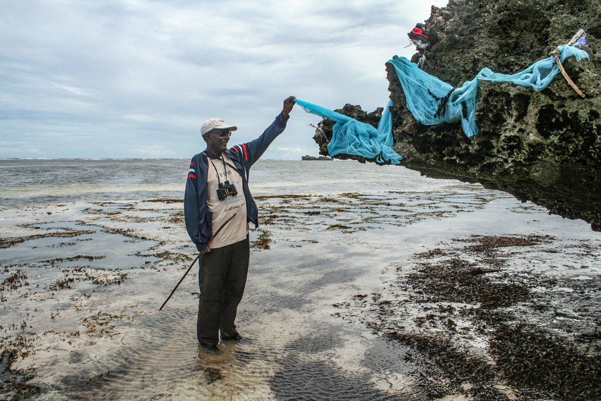 Liaison officer Athuman Abdalla holds discarded mosquito net used destructively for fishing. Photo by Amy Yee.
