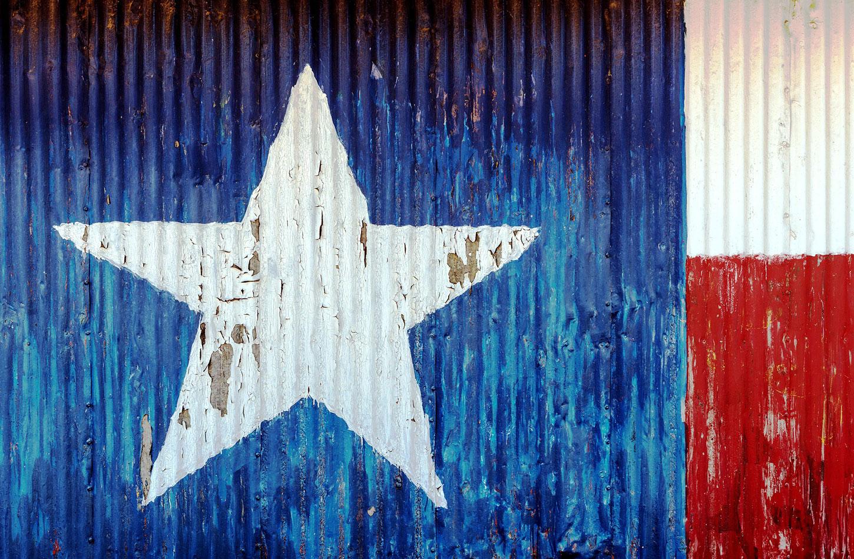 Texas flag painted onto corrugated metal and peeling