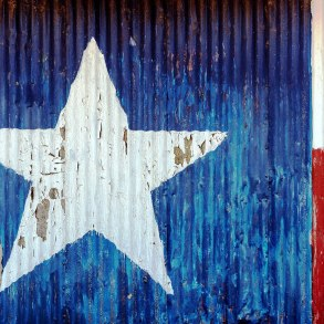 Texas flag painted onto corrugated metal and peeling
