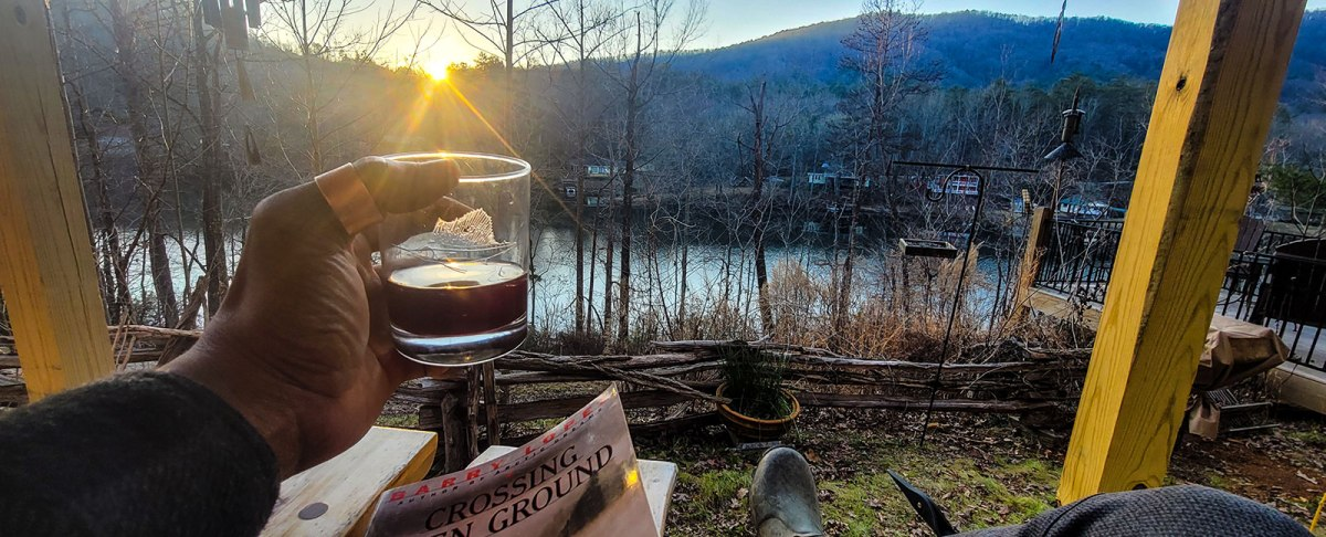 View of lake at sunset with whiskey in hand