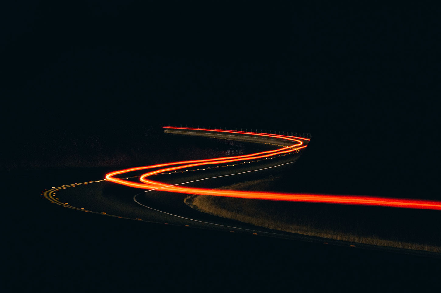 Taillights at night on winding road