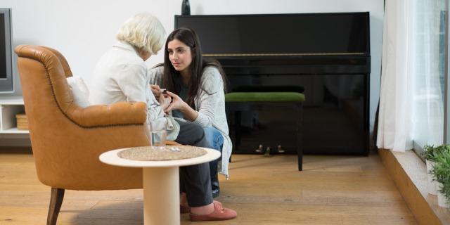 Cuidadora de una mujer con Alzheimer junto a ella dándole la medicación