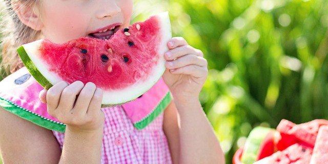 Niña comiendo una raja de sandía, una de las frutas más consumidas en verano.