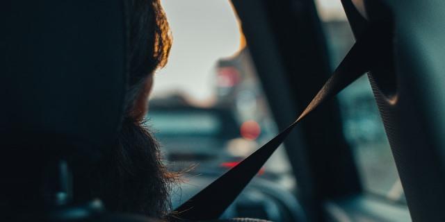 Persona circulando con el cinturón de seguridad puesto.