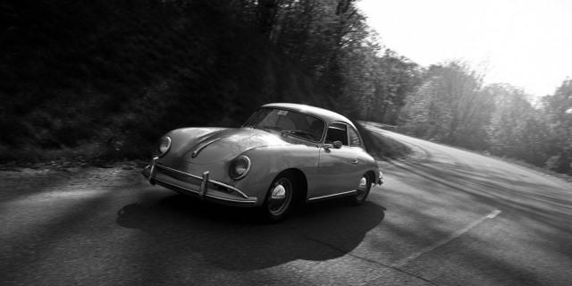 Coche escarabajo clásico circulando por una carretera.