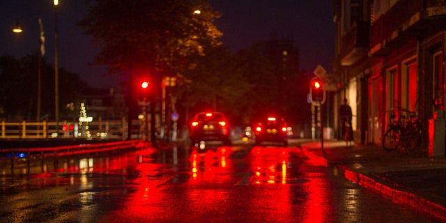 Coches parados en un semáforo por la noche.