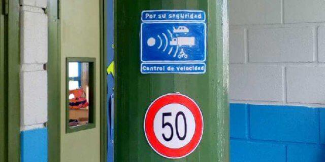 Dos señales de tráfico en una columna de un colegio.