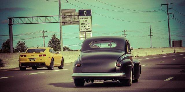 Coche clásicos circulando en una autopista.