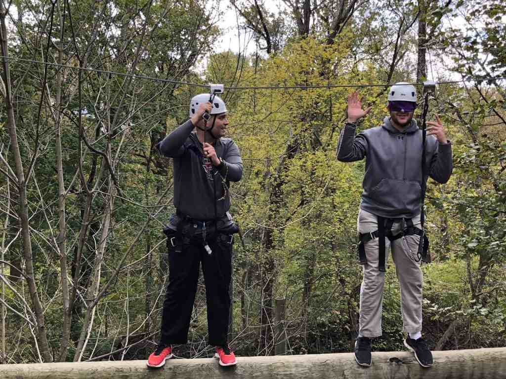 A man leading a blindfolded man on a high ropes challenge course.