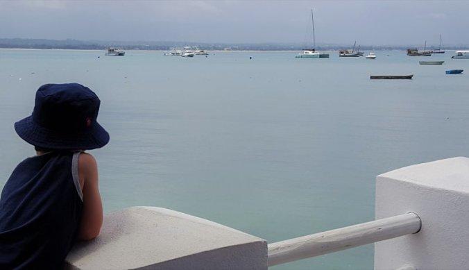 Julian kijkt naar de bootjes in de haven van Dar es Salaam