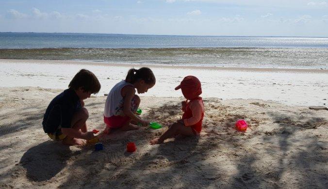 Kinderen spelen in het zand op Zanzibar