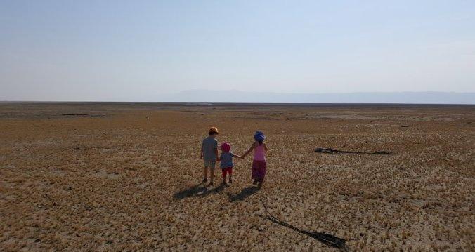 Kinderen wandelen op de uitgestrekte vlakte van Lake Eyasi