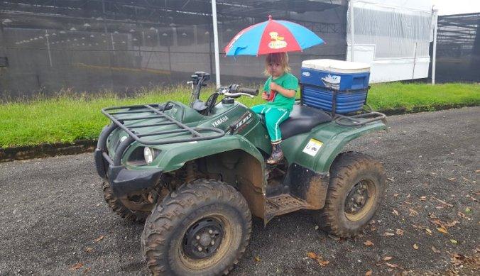 Op de quadbike met paraplu tijdens het regenseizoen