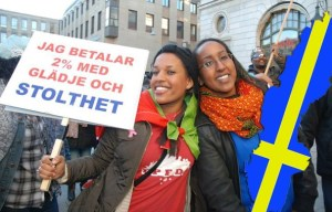 """Swedish-Eritrean citizen holding a sign that reads """"I pay 2% with joy and Pride"""""""