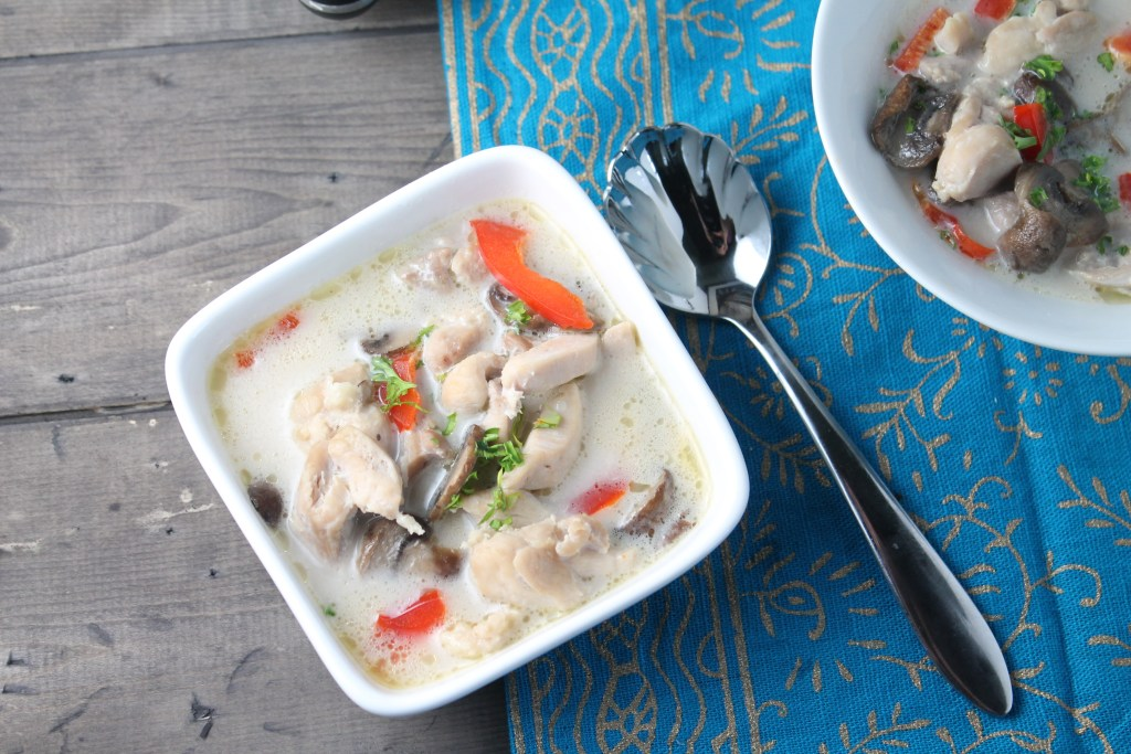 horizontal image of an overhead view of a square bowl of a coconut milk broth soup studded with tender bite sized pieces of chicken, fresh red bell pepper, mushrooms, and garnished with cilantro on a dark wooden surface
