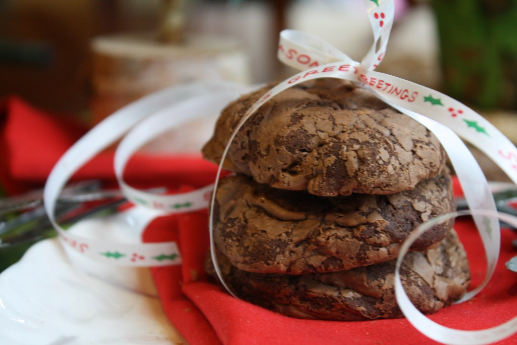 horizontal image of  three stacked chocolate cookies wrapped with a seasons greetings Christmas ribbon on a red linen from eye level and close up