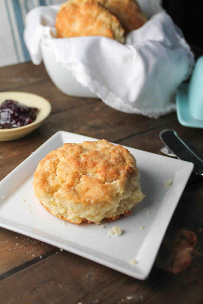 vertical image of flaky paleo biscuits on a dark wooden board with a butter dish and side of jelly