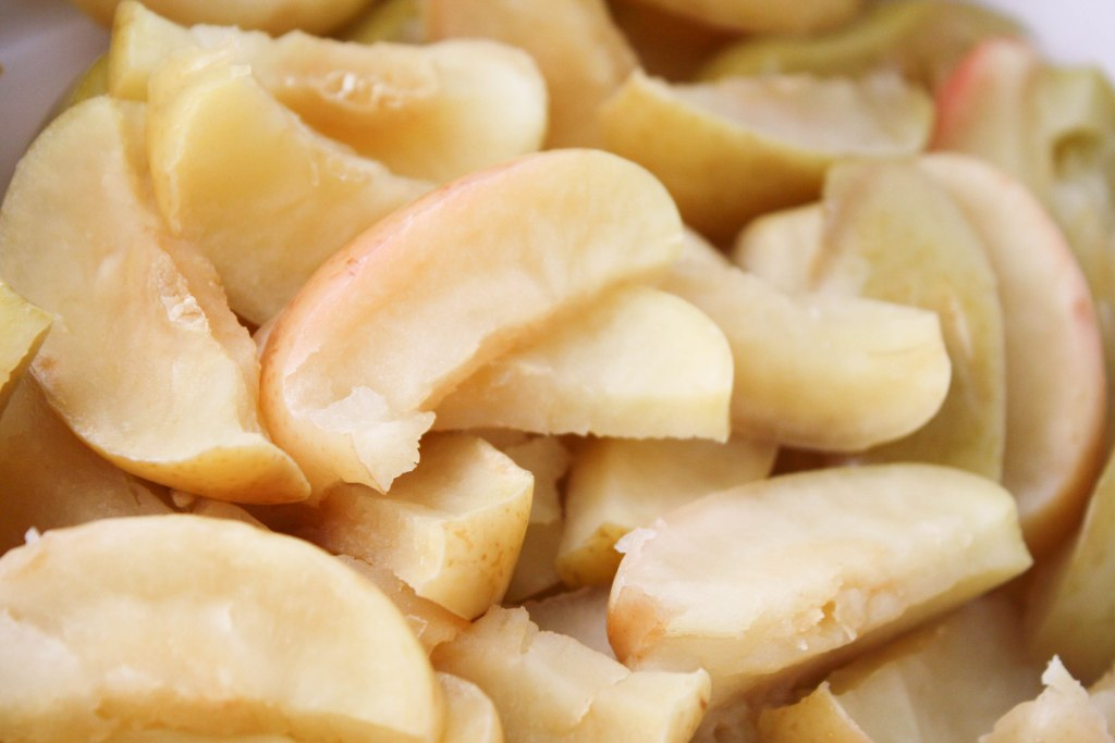 close up of cooked and wilted apple slices with the peels on