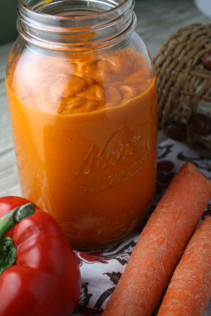 vertical image of a quart sized glass mason jar filled with roasted tomato sauce with a fresh pepper and carrot