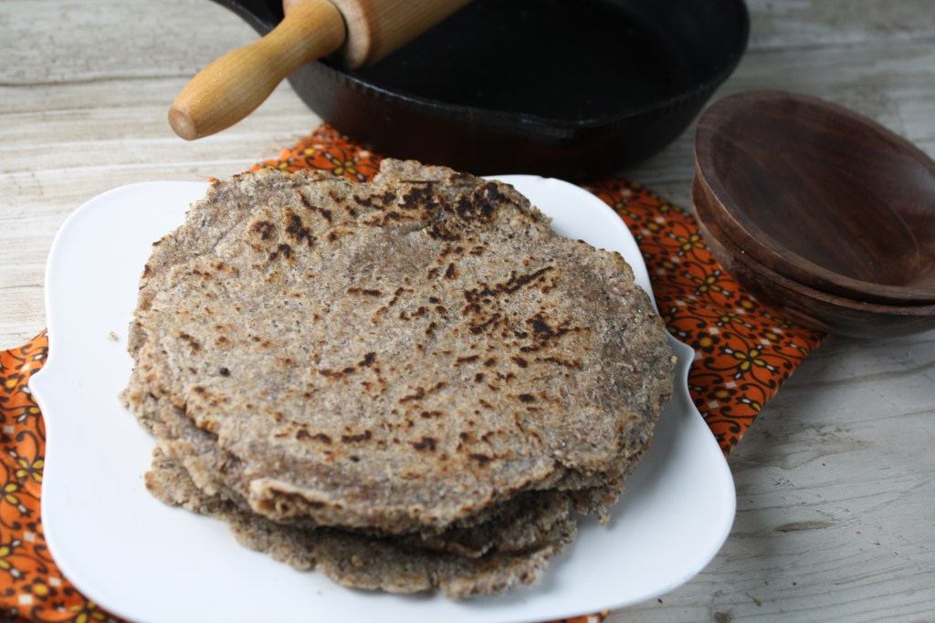 horizontal image of a stack of light brown wholegrain paleo tortillas on a white plate with a cast iron pan and wooden rolling pin in background