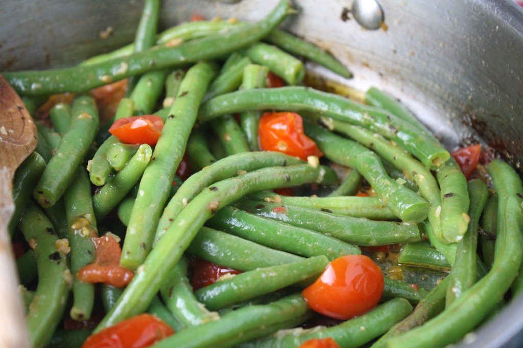 fresh green beans with cherry tomatoes and basil in a stainless steel cooking pan