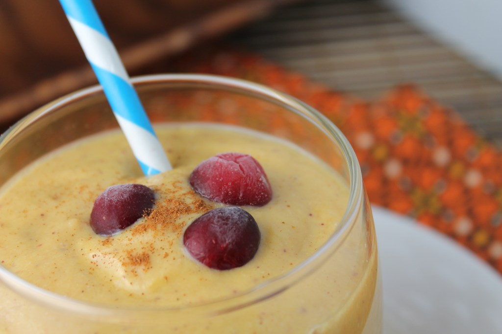 horizonatal image close up of a creamy orange hued pumpkin smoothie topped with a sprinkle of cinnamon and fresh whole cranberries with a pumpkin orange floral cloth