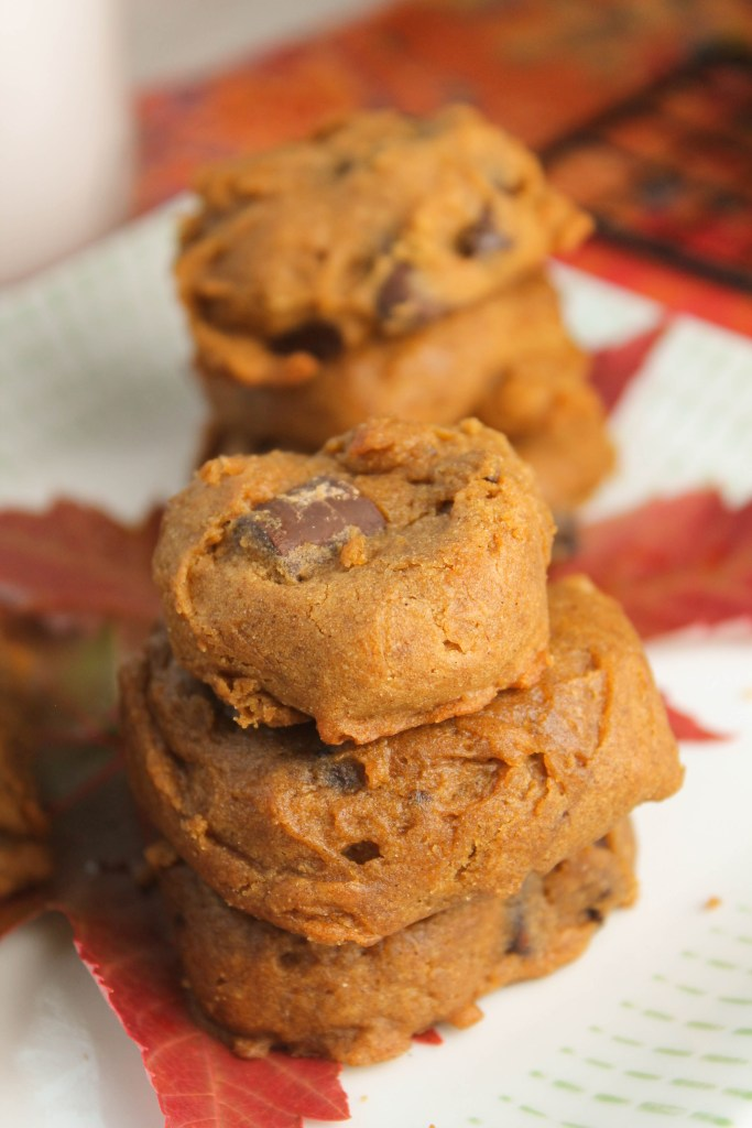 vertical image of stacked orange hues and chocolate studded gluten free pumpkin cookies
