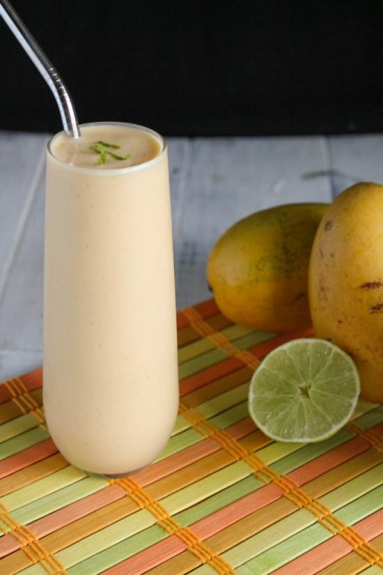 frosty orange mango lime kombucha smoothie with a wedge of lime and thai mangoes