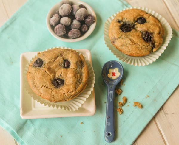 an overhead shot of 2 grain free blueberry muffins on a turquoise cloth in a paper baking cup